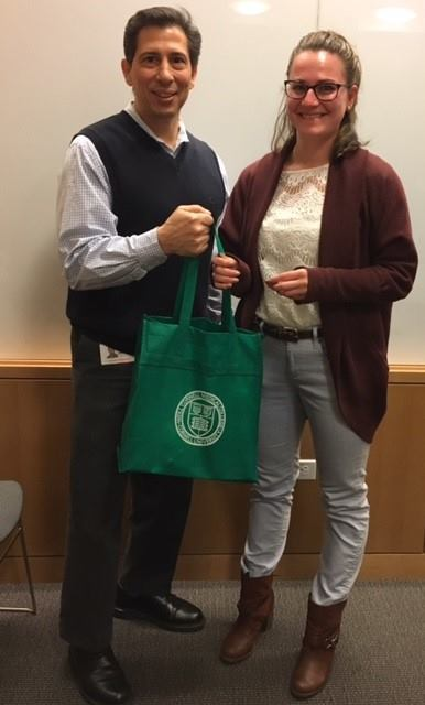 Man and woman posing for photo with green bag